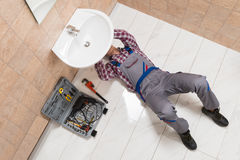Male Plumber Lying On Floor Repairing Sink In Bathroom. High Angle View Of Male Plumber Lying On Floor Repairing Sink In Bathroom royalty free stock photo