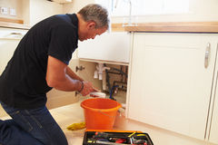 Male plumber preparing a pipe for the sink in a kitchen stock photography