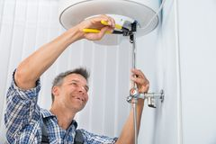 Male plumber repairing electric boiler Royalty Free Stock Photo