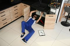 Male plumber repairing kitchen sink. Above view stock photography