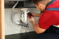 Male plumber repairing kitchen sink. With pipe wrench royalty free stock images