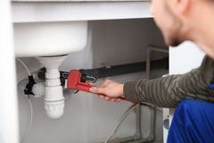 Male plumber repairing kitchen sink with pipe wrench. Closeup stock photography