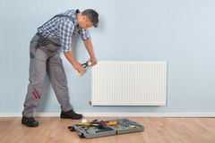 Male plumber repairing radiator Royalty Free Stock Photography