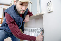 Male plumber repairing radiator with wrench. Man looking at the camera. Close-up Stock Image