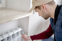 Male plumber repairing radiator with wrench. Worker looking at the radiator. Close-up Royalty Free Stock Photography