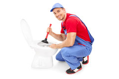 Male plumber unclogging a toilet with a plunger Royalty Free Stock Photography