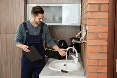 Male plumber in uniform checking faucet in kitchen. Repair service royalty free stock photography