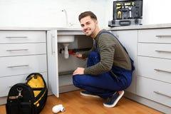 Male plumber repairing kitchen sink. Male plumber in uniform repairing kitchen sink stock photo
