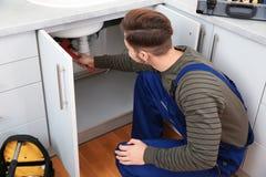 Male plumber repairing kitchen sink. Male plumber in uniform repairing kitchen sink stock photography