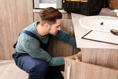 Male plumber in uniform repairing kitchen sink. Closeup royalty free stock images