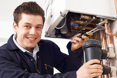 Male Plumber Working On Central Heating Boiler. Male Plumber Works On Central Heating Boiler stock photography