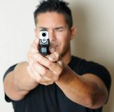 Male pointing gun. Image of young male pointing gun.  Focus on barrel of gun Royalty Free Stock Photography