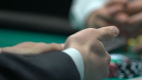 Male poker player betting money on low cards, reckless amateur gambler, closeup. Stock footage stock video footage