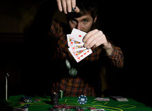Male poker player holds five cards, winning combination. on a dark background.  Royalty Free Stock Image