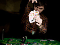 Male poker player holds five cards, winning combination. on a dark background.  Royalty Free Stock Photos