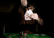 Male poker player holds five cards, winning combination. on a dark background.  Stock Photo