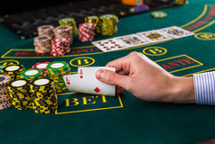 Male poker player lifting the corners of two cards aces Royalty Free Stock Image