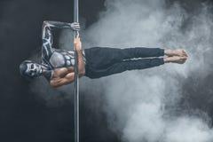 Male pole dancer posing in dark studio Royalty Free Stock Image
