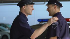 Male police companions greeting each other before start of shift, friendship. Stock footage stock video footage