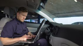 Male police officer working on laptop in car, filling data in crime report stock footage
