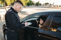 Male police officers check vehicle on the road. Male police officers in uniform check vehicle on the road. Law protection, car traffic inspector, safety control stock photo