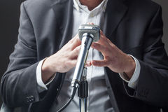 Male politician talking on a microphone with focus on his hands Royalty Free Stock Photo