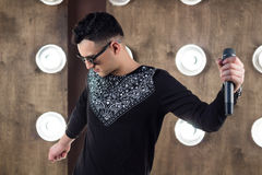 Male pop singer performs on scene in projectors lights. Male singer of rock or pop music dressed in black and sunglasses with microphone performs on scene with Royalty Free Stock Photo