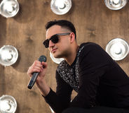 Male pop singer sings on scene in projectors lights. Male singer of rock or pop music dressed in black and sunglasses with microphone performs on scene with Stock Photos
