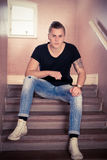 Male portrait sitting on stairs. Male portrait in t shirt, sitting on stairs Stock Image