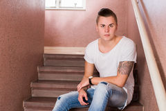 Male portrait sitting on stairs. Male portrait in t shirt, sitting on stairs Stock Images