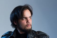 A stern gaze of a guy in a black leather jacket with a beard and long hair in the style of rock`n`roll. Male portrait in royalty free stock image