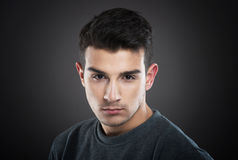 Male portrait. Studio portrait of a serious young man looking at camera, dark background Stock Photography