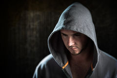 Male portrait. Young male posing wearing hoodie with dark moody lighting and sombre mood Royalty Free Stock Photo