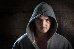 Male portrait. Young male posing wearing hoodie with dark moody lighting and sombre mood Royalty Free Stock Photos