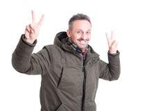 Male posing wearing winter jacket showing peace gesture Stock Photo