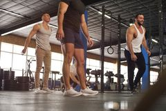 Male Positive Muscular Friends Working Out in Gym. stock photo