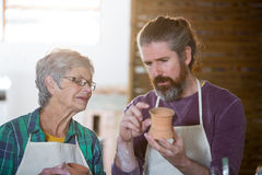 Male potter assisting female potter for making pot Stock Photography