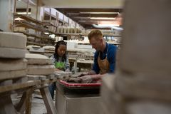Male potter assisting girl in molding a clay Stock Photos