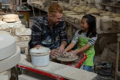 Male potter assisting girl in molding a clay Stock Photo
