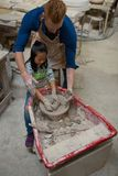 Male potter assisting girl in molding a clay Stock Image