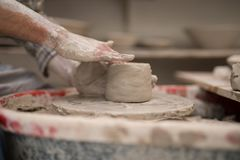 Male potter molding a clay. Close-up of male potter molding a clay in pottery workshop Royalty Free Stock Image