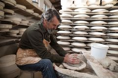 Male potter molding a clay. In pottery workshop Royalty Free Stock Photos