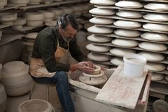 Male potter molding a clay. In pottery workshop Stock Photography