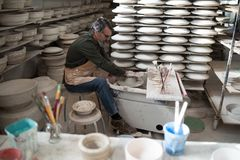 Male potter molding a clay. In pottery workshop Stock Images