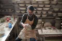 Male potter molding a clay. In pottery workshop Royalty Free Stock Photo