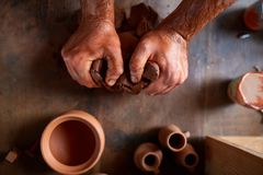 Male potter molding a clay in pottery workshop, close-up, selective focus, top view. Creative work process. Craftsman preparation for making a masterpiece at Royalty Free Stock Photography