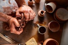 Male potter molding a clay in pottery workshop, close-up, selective focus, top view. Creative work process. Craftsman preparation for making a masterpiece at Stock Image