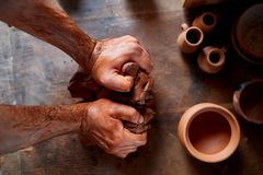 Male potter molding a clay in pottery workshop, close-up, selective focus, top view. Creative work process. Craftsman preparation for making a masterpiece at Royalty Free Stock Photo