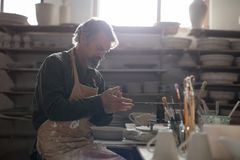 Male potter molding a clay. In pottery workshop Stock Image
