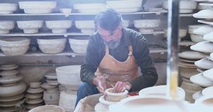 Male potter moulding a clay 4k